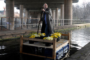 1_-_Bill_Drummond_making_his_ceremonial_entrance_into_Birmingham_on_a_raft_made_from_his_bed_and_400_bunches_of_daffodils_under_Spaghetti_Junction__2014_ref_P4990